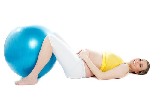 Beautiful pregnant woman lying with exercise ball