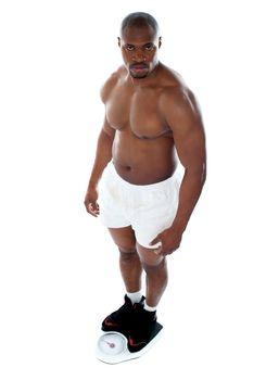 Muscular man standing on electronic weighing machine