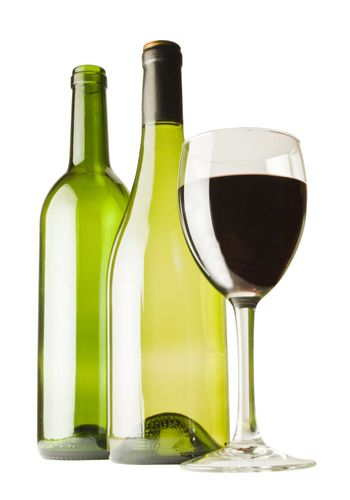 A glass of red wine with two wine bottles