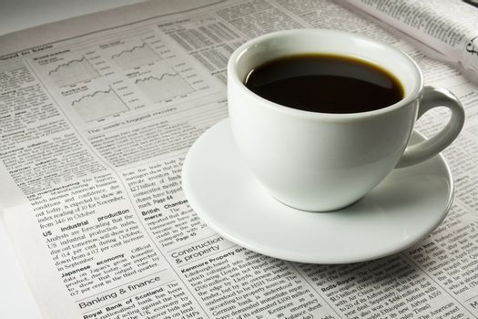 Cup of coffee standing on a newspaper.