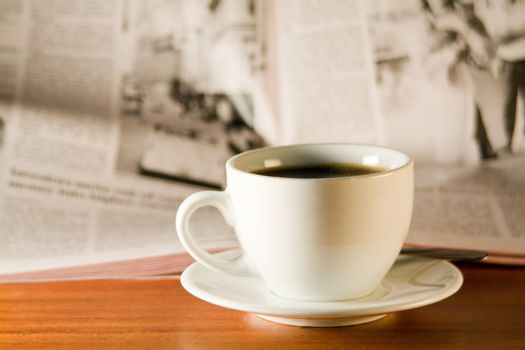 Coffee and newspaper on a wooden table. Small depth of sharpness.
