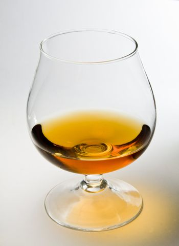 Snifter glass of cognac on white background.
