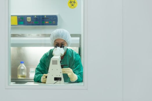 Woman at work with microscope in biotechnology laboratory