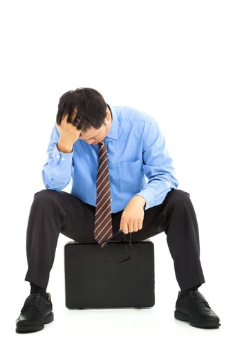 frustrated businessman sitting on the briefcase