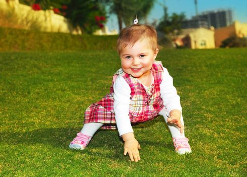 Sweet baby girl playing outdoor on the green grass