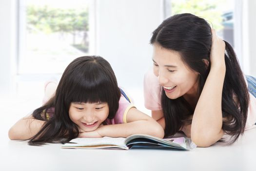 young  mother and her daughter lie on the floor and reading a bo