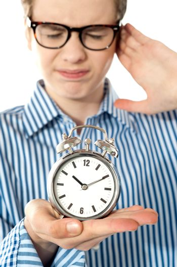 Boy irritated with noise of alarm clock
