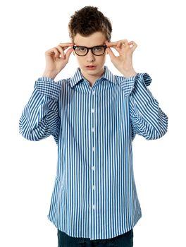 Young boy holding eyeglasses