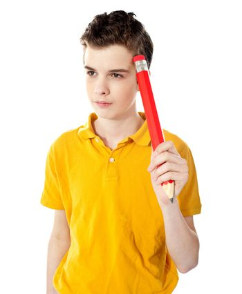 Thoughtful boy holding a pencil