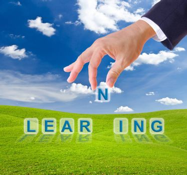 business man hand and learning word on green grass meadow