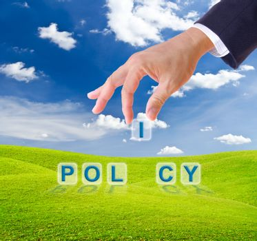 business man hand made policy word buttons on green grass meadow