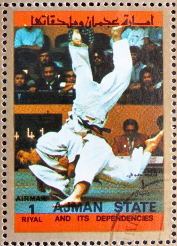 AJMAN - CIRCA 1973: a stamp printed in the Ajman shows Judo, Olympic sports, circa 1973