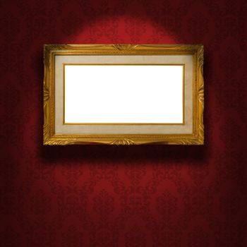 Empty golden frame illuminated from a spotlight. The frame is on the red damask wallpaper. Clipping path included.