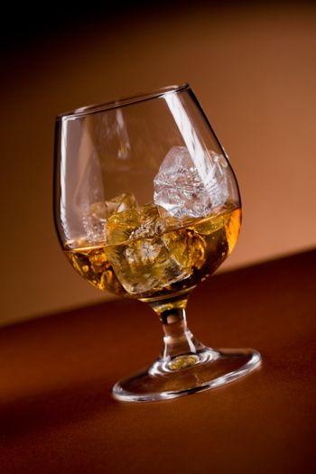photo of delicious glass of cognac whiskey with ice cubes on brown background