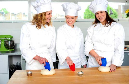 Professional chefs kneading bread dough