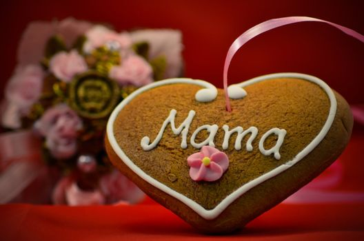 Mothers day gingerbread heart with bouqet in background