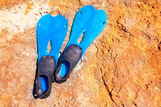blue scuba diving fins on summer day over rock