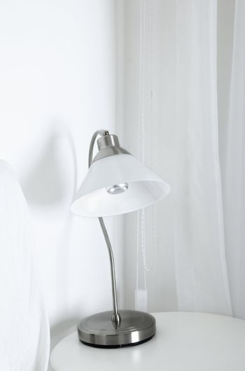 White table lamp in a white interior with wite curtain