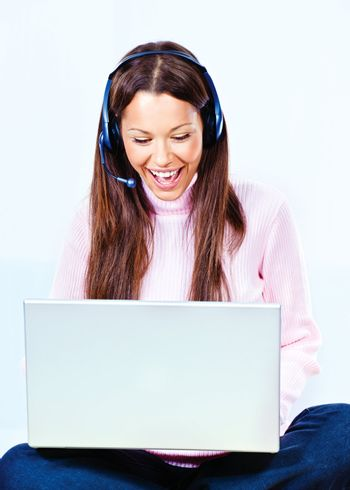 Happy young woman with headphones and  laptop at home