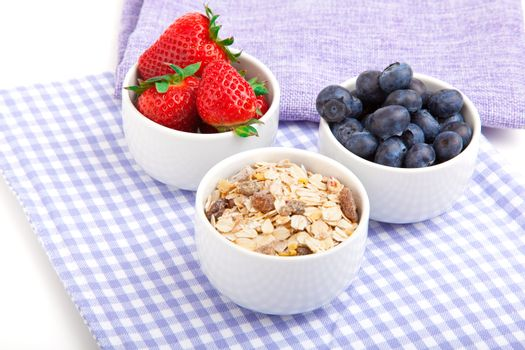 fresh blueberry, strawberries, corn flakes in the porcelain bowl