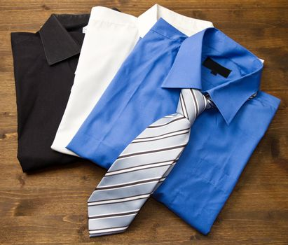 Close up of stacked shirts with tie on wood