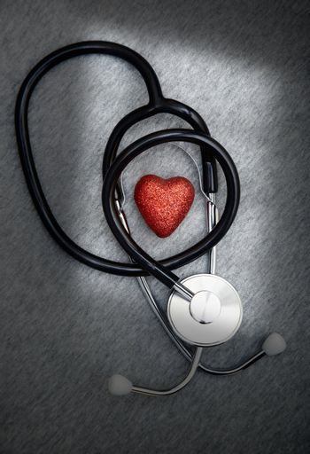 Stethoscope and heart symbol on a dark table with shadows