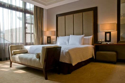 Bedroom of a elegant 5 star hotel suite room at a sunny day