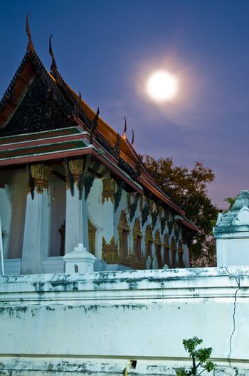 A Wat during night with full moon in the sky. Ayutthaya city is the capital of Ayutthaya province in Thailand. Its historical park is a UNESCO world heritage.