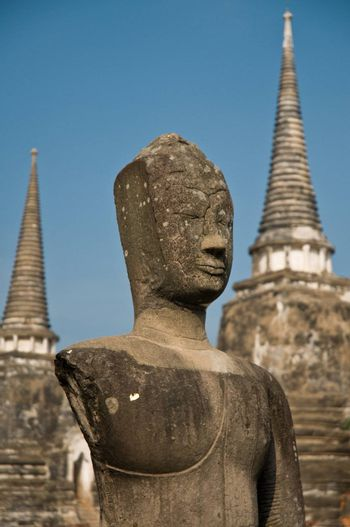 Stupa (chedi) of a Wat in Ayutthaya, Thailand, with Buddha staue. Ayutthaya city is the capital of Ayutthaya province in Thailand. Its historical park is a UNESCO world heritage.