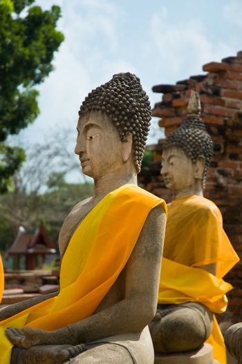 Two Buddha statues wrapped in an orange scarf. Ayutthaya city is the capital of Ayutthaya province in Thailand. Its historical park is a UNESCO world heritage.