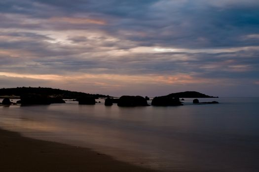Twilight after a sunset at a beach, with long exposure, rock formation in the water