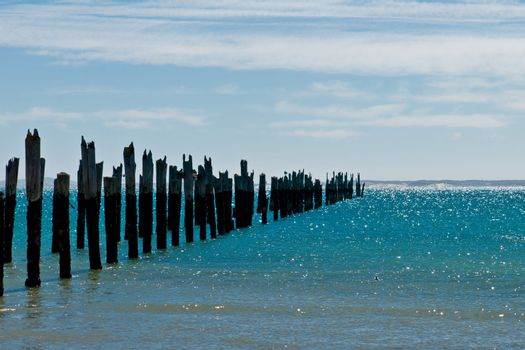 Beautiful rotten mooring on a beach where only the pillars are left over at a bright sunny day