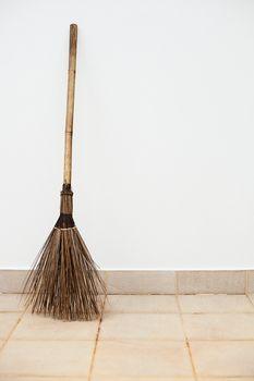 A large a broom near a white wall