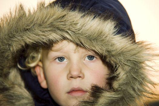 Little boy wearing a fur lined hood
