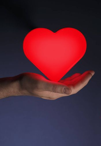Man holding a red glowing heart shape in his hand.
