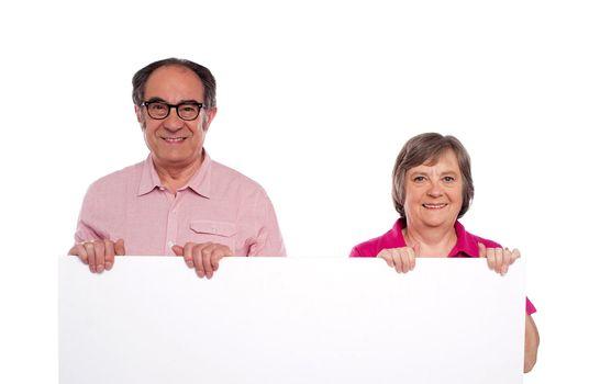 Aged couple displaying blank billboard