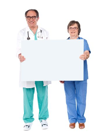 Aged doctors displaying white billboard