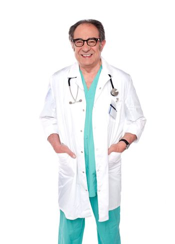 Aged surgeon with hand in pocket