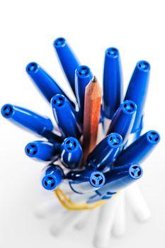 Sharpened pencil between pens in caps.