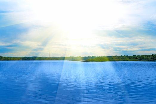 Lake, green field, sun and blue sky