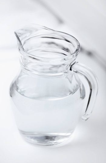 Transparent glass can with water on a table with shadows