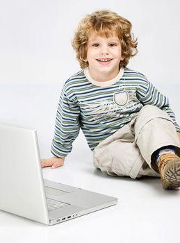 Blue curl hair boy seating near laptop
