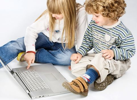 girl and boy seating near laptop