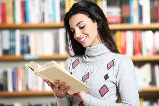 smiling female student with book in hands in a bookstore