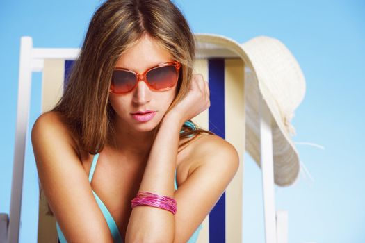 Young woman with sunglasses on beach chair