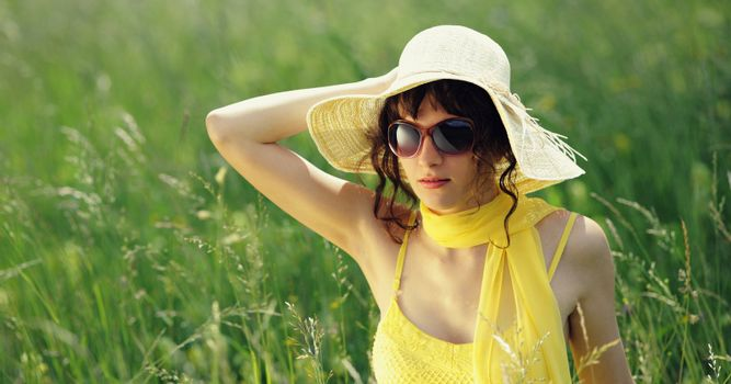 young woman in sunglasses in a flowers field