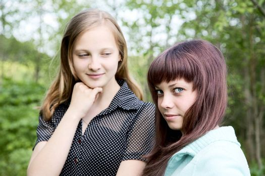 Two girls of the teenager in  spring afternoon against green foliage