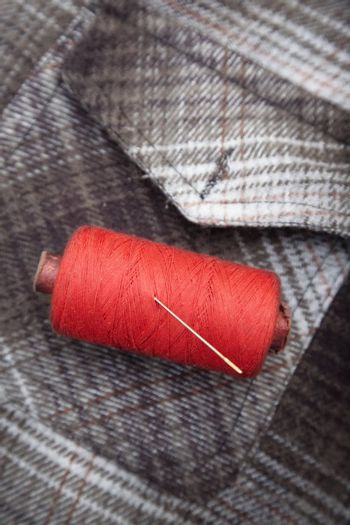 Red sewing spool with needle on a flannel fiber. Close-up photo