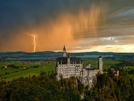 Landscape with Neuschwanstein castle. Thunderstorm with rain and lightning on background