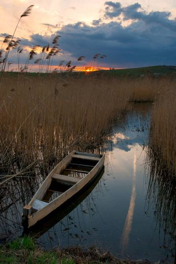 The lonely boat on the river, evenig sky with sunrise and clouds on background, outdoors